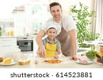 dad and son cooking at home | Shutterstock . vector #614523881