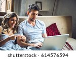 young happy couple sitting on... | Shutterstock . vector #614576594