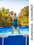 Small photo of Fun weekend alfresco. happy active woman in blue swimsuit in the swimming pool jumping