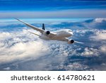 Small photo of The passenger plane in flight. Aircraft flies high in the blue sky over clouds. Front view.