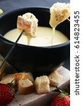 Small photo of Gourmet Swiss fondue dinner with assorted cheeses on a board alongside a heated pot of cheese fondue with two forks dipping bread and white wine behind in a tavern or restaurant