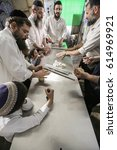 Small photo of Safed, Israel - April 4, 2017: Orthodox Jews rolling dough for Matzahs for Passover prior to putting in oven. Jewish men prepare hand-made glat kosher matzah