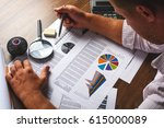 Small photo of The man (businessman, manager, analyst, student) working with tables, graphs, diagrams, makes calculations at the wooden table in the office in the evening (or at night), after hours