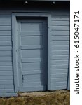 Small photo of Wood paneled door against wood exterior wall, all the same blue-ish color. with shadows from roofline.