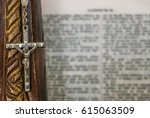 Small photo of Christian and catholic Jesus Christ cross crucifix rosay made of wood and jewelery with an open bible in the background - Religion, catholicism, belief, god concept and idea