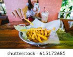 woman eating french fries while ... | Shutterstock . vector #615172685