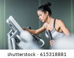 Small photo of Side view portrait of beautiful sportive woman exercising using elliptical machine during intense workout in modern gym
