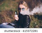 blonde girl vaping outdoors .... | Shutterstock . vector #615372281