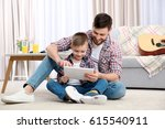 father and his son with tablet... | Shutterstock . vector #615540911