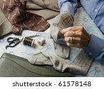 man at home table darning socks - stock photo
