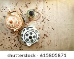 Small photo of 3 various traditional ceramic teapots on a canvas background with copy space. Group of cute steaming clay-ware pots with hot tea among tea leaves and berries scattered on fabric