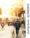 Stock photo senior man leashing a bull dog walking in town 615883835