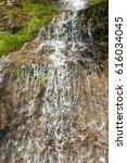 Small photo of Small abounding in water mountain rocky waterfall in early springtime