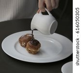 Small photo of A jug with hot chocolate and two eclairs with cream on a plate on a table in a cafe. girl is pouring the eclair by chocolate