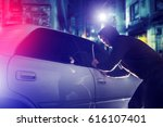 car thief in action at night. Car Security Theme. - stock photo