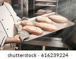 the baker takes the hot bread... | Shutterstock . vector #616239224