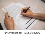 Small photo of Man's hand is filling in document