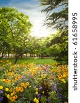 Stock photo parterre plenty of flowers rounded by trees at sunset 61658995
