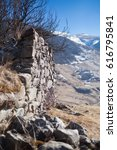 Small photo of Stone wall in the mountains near the village of Dargavs. North Ossetia - Alania, Russia. With background of mountains and blue sky. Selective focus.