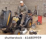 Small photo of NICA, LATVIA - APRIL 7, 2017: Young man is repairing lawn mower starting engine with extra accumulator and charger