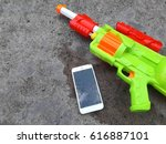 Small photo of Water gun and smartphone. Modern mobile smartphone broken screen and damages in the Songkran Festival.