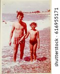 Small photo of USSR, ABKHAZIA, LESELIDZE - CIRCA 1979: Vintage photo of dad with little daughter on Black sea beach in Abkhazia, USSR