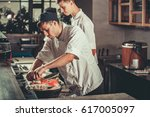 two young white chefs dressed... | Shutterstock . vector #617005097