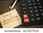 Stock photo paper sheet with text tax deadline calculator and pencils on wooden table 617027924