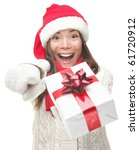 Christmas woman holding / giving gift excited pointing. Happy smiling woman in santa hat giving you a present being joyful, fresh and cheerful. Asian / Caucasian model isolated on white background. - stock photo