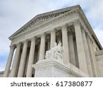 Small photo of Looking up at the U.S. Supreme Court with justice statute in foreground