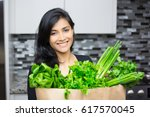 Small photo of Closeup portrait, young woman with bag full of green groceries, healthy nutritious balanced diet, isolated indoors home background. Locally sourced food