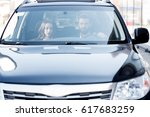 Small photo of Business couple having a conversation while driving a car. Front view through the windshield