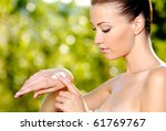 beautiful woman applying on hand cosmetic cream. Green natural background - stock photo
