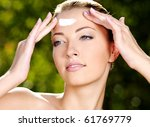 Beautiful sexy woman with fresh health skin applying cream on forehead - Outdoors - stock photo