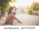 beautiful asian girl riding... | Shutterstock . vector #617774729