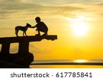 Stock photo silhouette little boy and his dog on side shipwreck aground on sea sand sun going down light 617785841
