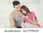upset couple sitting on bed and ... | Shutterstock . vector #617799419