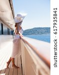 woman on a boat deck with a hat  | Shutterstock . vector #617935841