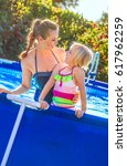 Small photo of Fun weekend alfresco. happy active mother and child in swimsuit in the swimming pool looking at each other
