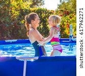 Small photo of Fun weekend alfresco. happy healthy mother and child in swimsuit in the swimming pool playing