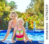 Small photo of Fun weekend alfresco. Portrait of happy active mother and daughter in beachwear standing in the swimming pool