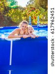 Small photo of Fun weekend alfresco. Portrait of cheerful active mother and daughter in swimwear in the swimming pool