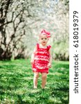 Small photo of cute happy baby girl in funny pink romper walking outdoor in spring garden. Happy childhood concept