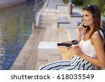 young woman relaxing alongside...   Shutterstock . vector #618035549