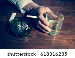 Small photo of Hand of a man in the bar holding glass with alcohol drink and cigarette. Addiction. Addict. Abuse.