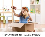 Small photo of Kid child pilot flying a cardboard box in kid room