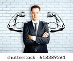 Small photo of Confident businessman with drawn muscly hands on brick background. Strength concept