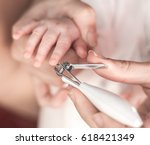 mother carefully cut the nails... | Shutterstock . vector #618421349