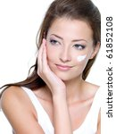 Beautiful woman with moisturizer cosmetic cream on face - on a white - stock photo