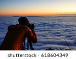 a man taking a photo at sunrise | Shutterstock . vector #618604349